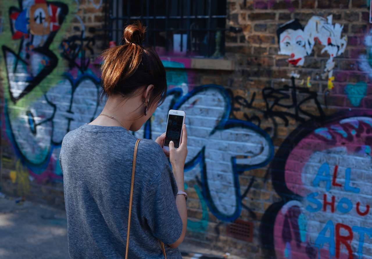 Girl taking a photo of an art wall