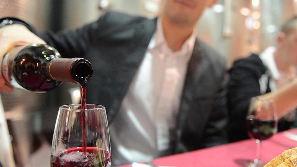 Man pours red wine at gala