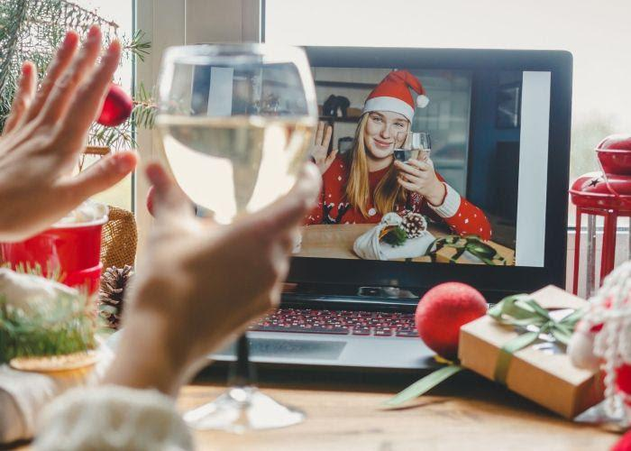 A woman playing a virtual White Elephant, with a glass of wine in her hand.